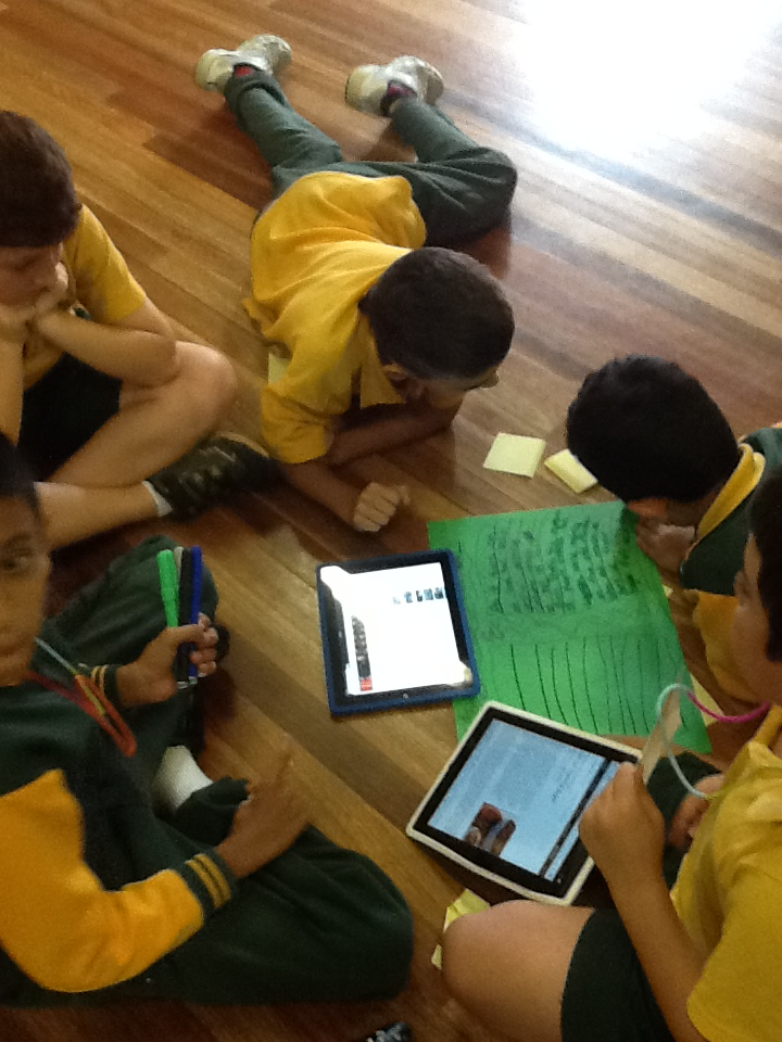 Students with tablets and posters working together